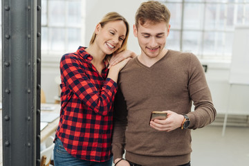 Affectionate couple looking at a mobile phone