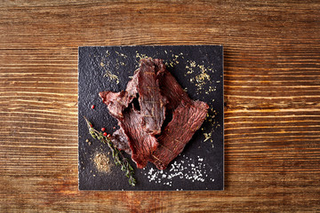Dried peppered beef jerky cut in strips on the black board on wooden background