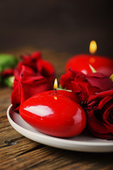 Red candles and roses on the wooden table