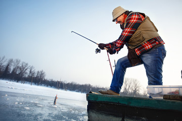 Fisherman draws hooked fish from frozen water