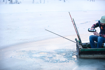 Fisherman fishing in frozen river on winter and drinking tee