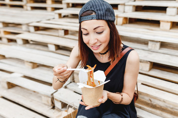 Beautiful woman student eating asian fastfood from paper box with Delicious chinese Wok noodles