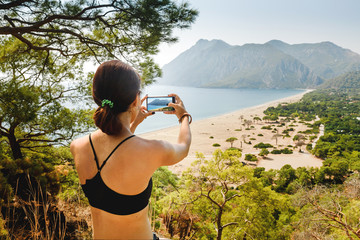 woman photographing an idyllic seascape with the beach and mountains in Turkey