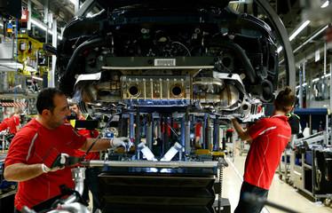 Employees of German car manufacturer Porsche work on a Porsche 911 Carrera 4S at the Porsche factory in Stuttgart-Zuffenhausen