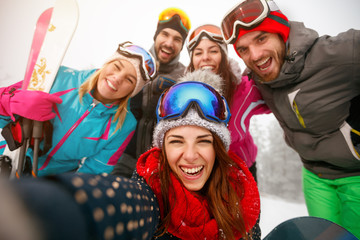 Group of friends making selfie and having fun on the snow