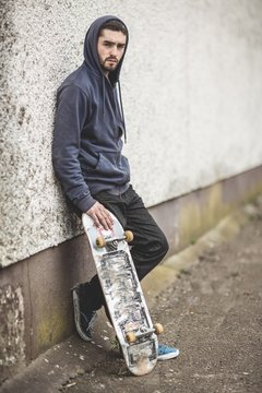 Skater leaning against wall