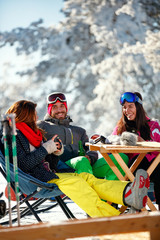 Cheerful friends having fun after skiing in resort with snow equipment