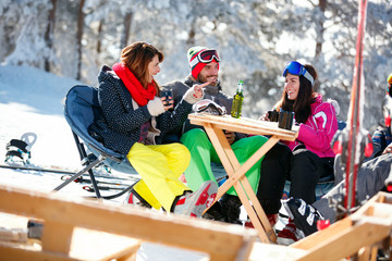 Happy friends spending time together and drink after skiing in cafe at ski resort