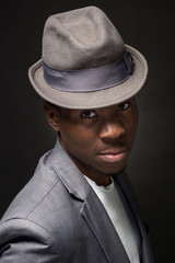 Close-up portrait of handsome black man with charming smile. Studio shot of well-dressed african guy wears hat and jacket.