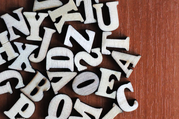 Pile of wooden letters over the wooden surface as a typography background composition