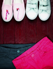 Two pairs of textile shoes in a sports style and two pairs of shorts of pink and mint color