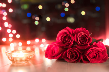 Beautiful roses next to candle light.