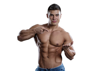 A smiling male bodybuilder points to his open palm. The picture is suitable for advertising sports goods and services.