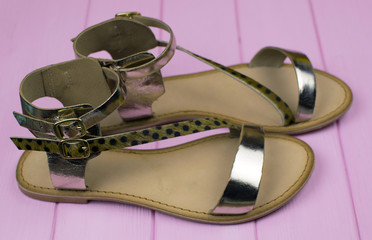 golden open sandals in Roman style with fur ponies on a pink wooden background