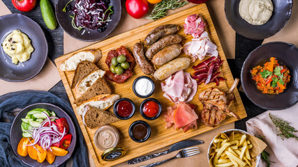 Assorted foodset from sausages, vegetable salad, french fries, Rack of lamb, pastrami, mashed potatoes, chicken pate
