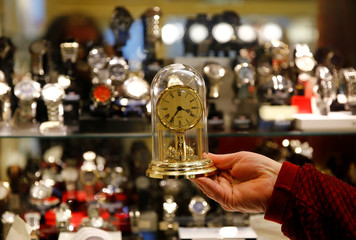 A watchmaker holds a clock in his store in Vienna