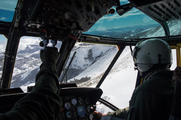 Military helicopter flying through white snowed mountains, pilot and copilot wearing green flightsuit and helmet view