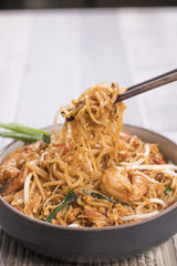 Close up of Pad Thai noodle being picked up by chopsticks