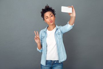 Young african woman isolated on grey wall studio casual daily lifestyle selfie picture