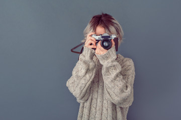 Young woman in a woolen sweater isolated on grey wall winter concept taking photos