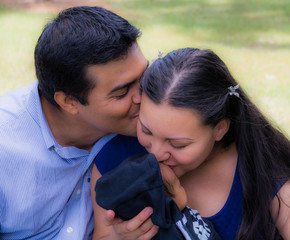 Latino Husband kisses his wife while Latina Wife kisses her newborn