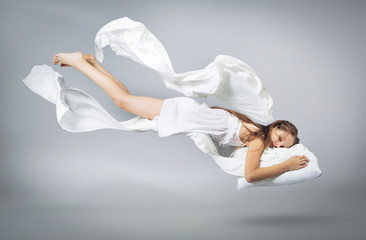 Sleeping girl. Flying in a dream. White linen flying through the air.