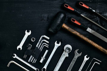 Flat lay of set of tools for car repairing such as wrenches on black wooden background. Top view.