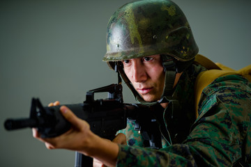 Portrait of young soldier holding in his hands a rifle, wearing a military uniform, in a gray background