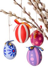 Easter eggs on willow bouquet with catkins, vertical. Four hand-painted colored Paschal eggs on branches of sallows or also called osiers, with aments. Photo on white background.