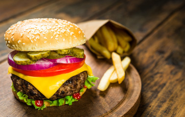 Burger with cheese and french fries against wooden background. Tasty unhealthy and fast food.