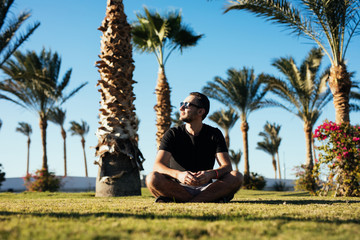 Handsome young bearded man in sunglasses sitting on the grass under palms on summer vocation luxary resort