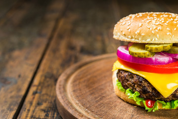 Burger with cheese against wooden background. Tasty unhealthy and fast food.