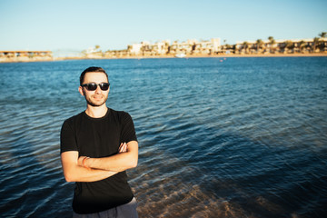 Young handsome man wearing spectacles and having fun on sea beach