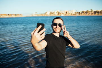 Young handsome man doing a self-portrait victory sign with smartphone on background of sea beach