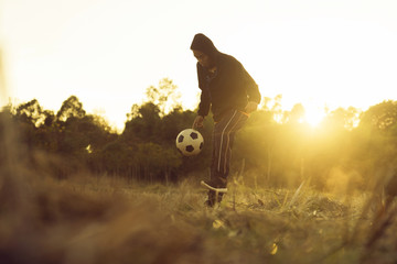 Soccer player in action on sunset with field in the countrysude