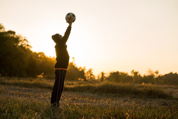 Asian boy playing football soccer in the meadow with sunset background