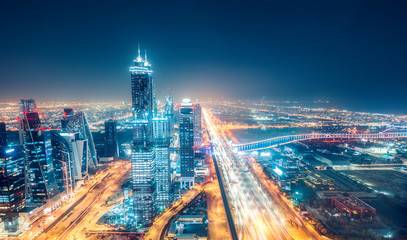 Scenic nighttime skyline of big cmodern city with illuminated skyscrapers. Aerial perspective of downtown Dubai, UAE. Multicolored travel background.