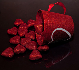Shiny red hearts spilling out of a red cup with a white heart on it on a black reflective background