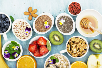 Ingredients for healthy breakfast, nuts, oatmeal, honey, berries, fruits, blueberry, orange, Edible flowers, Chia seeds, flax seeds, goji berries, almond, walnut. The concept of natural food. Top view