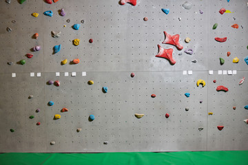 Climbing wall with colorful grips and green mat near by