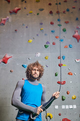 Attractive young man with curly hair holding by rope for climbing before training