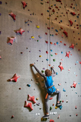 Contemporary man in activewear hanging on rope while climbing wall at leisure
