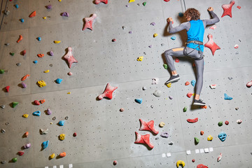 Back view of young adventurer in activewear holding by grips while climbing wall