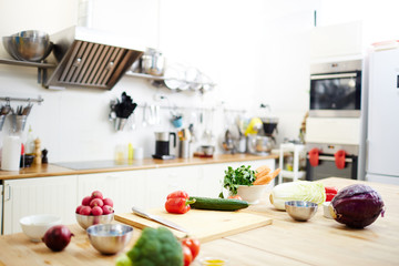 Variety of fresh vegetables on workplace of chef in the kitchen
