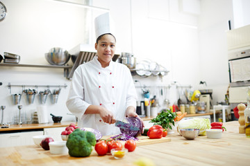 Young woman in chef uniform cooking fresh vegetable salad while cutting purple cabbage