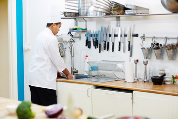 Chef washing vegetables over sink in the kitchen during work
