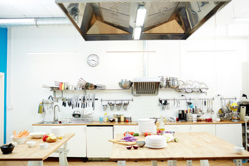 Workplace of chef with tables and kitchenware and some fresh vegetables for cooking