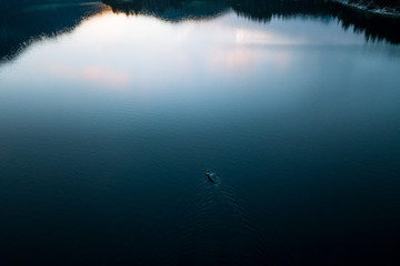 Aerial view of Father and son in kayak on lake Eibsee in Germany during sunset with forest and mountains