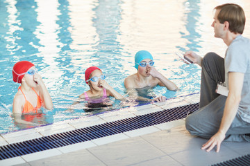 Group of kids in swimwear listening to their trainer while learning to swim