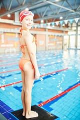 Cute smiling girl in swimwear looking at camera while standing on diving board and going to jump into water
